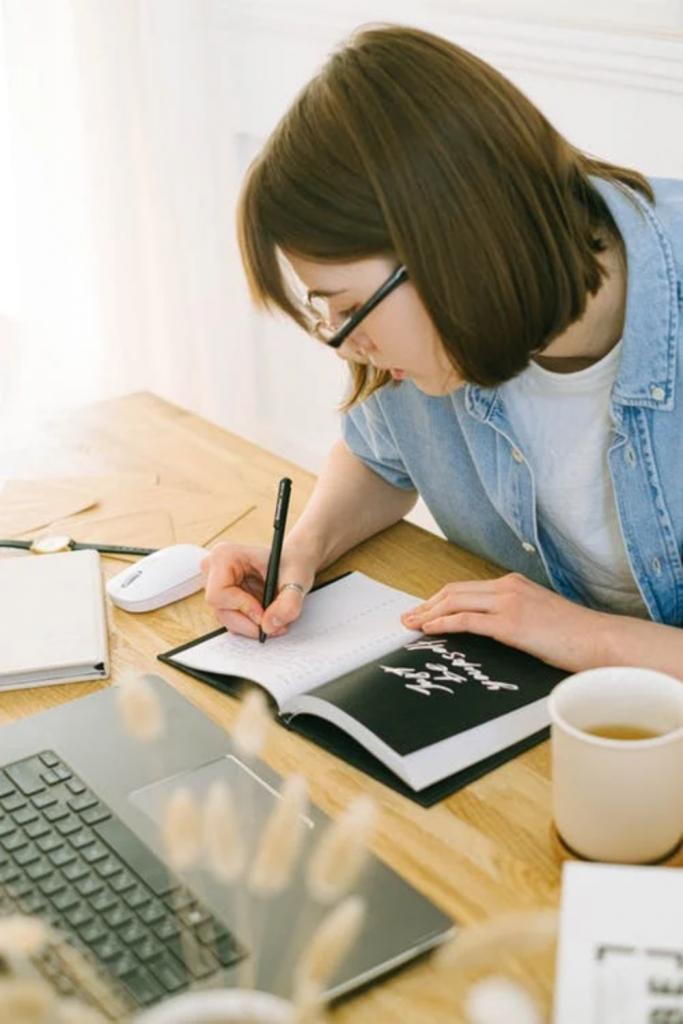 Woman writing in notebook image for orange & bergamot