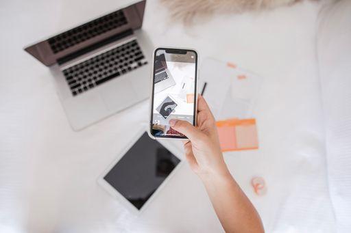hand holding phone capturing laptop and ipad image for orange & bergamot